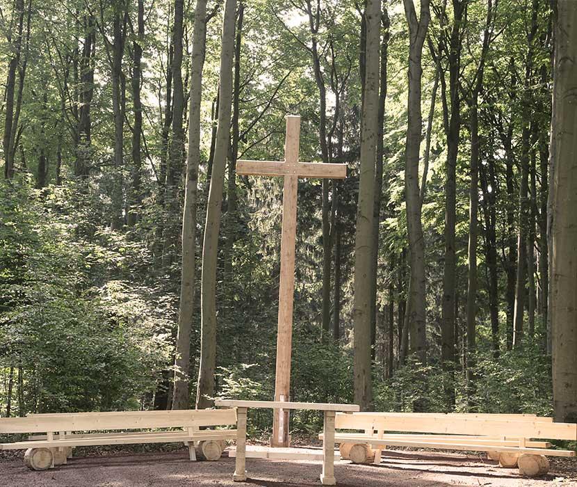 Andachtsplatz mit hölzernem Kreuz und Bänken sowie dem Wald im Hintergrund